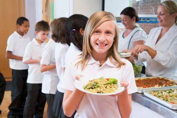 school girl holding plate of lunch