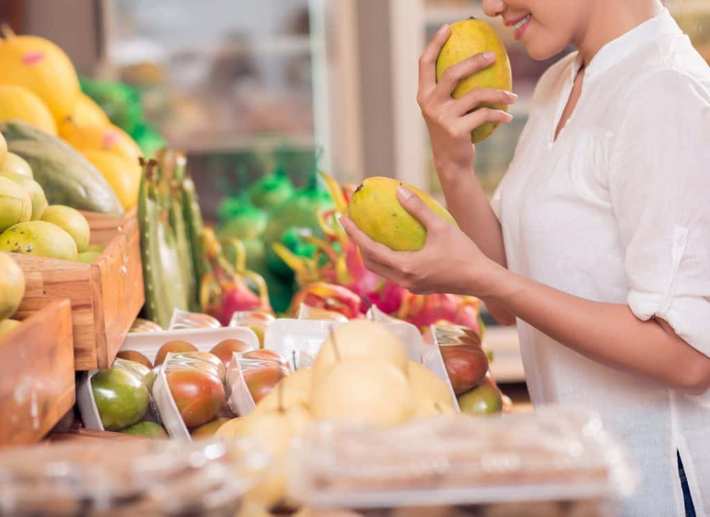woman smelling fruit at a local market