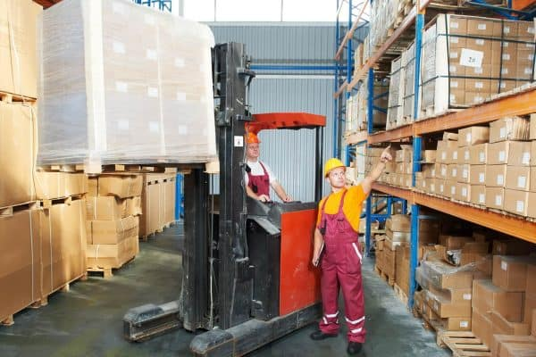 warehouse workers operating forklift as part of supply chain
