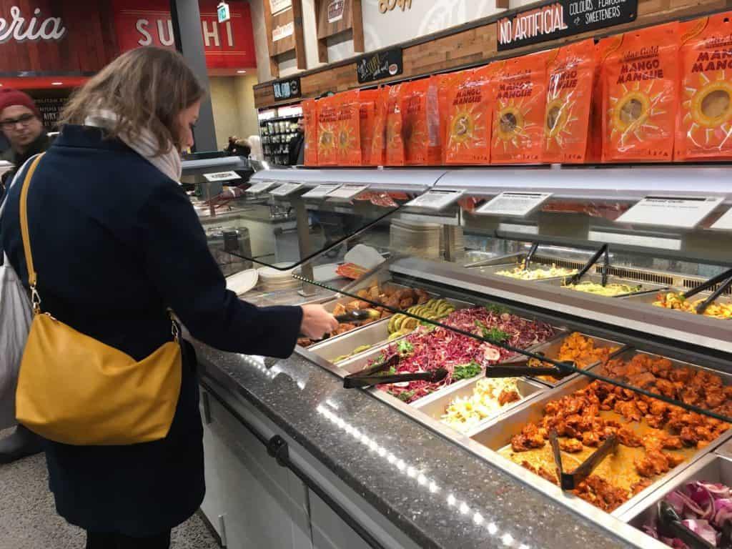 Woman selecting hot food at supermarket