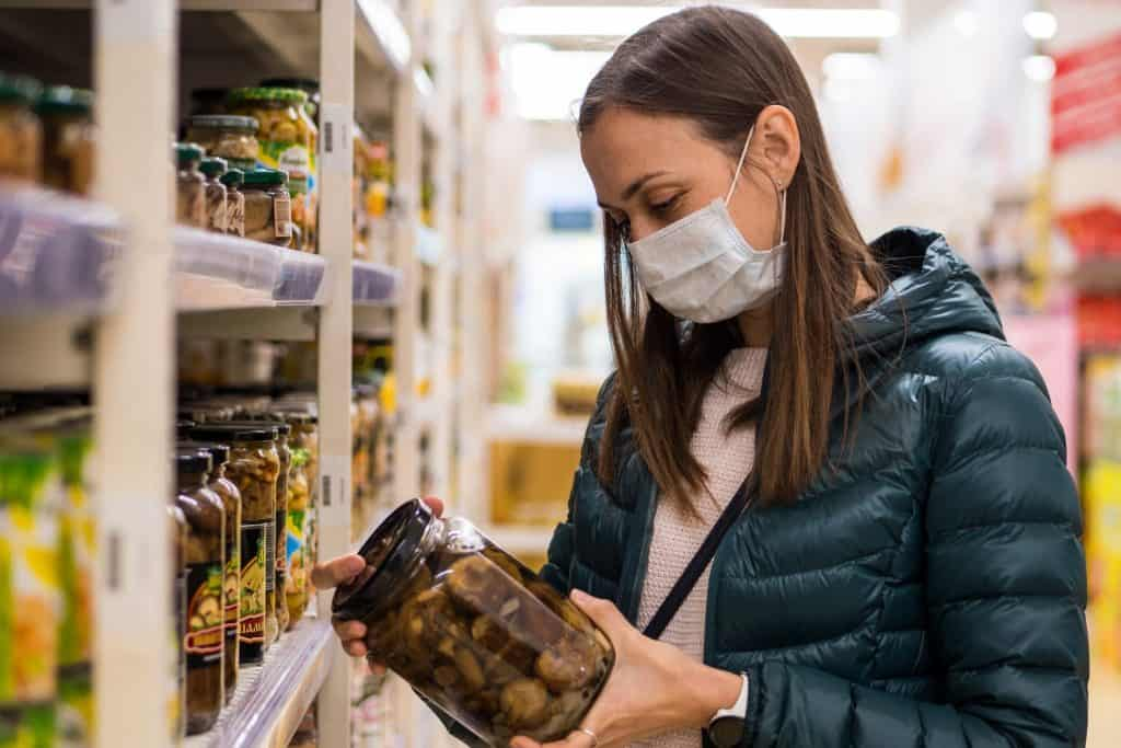 Young woman in medical mask in grocery store because of Covid 19